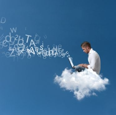 A man working on a computer and sitting on a cloud.