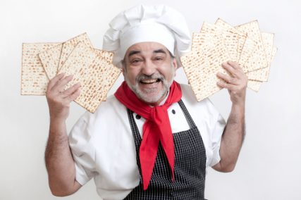 A smiling chef with matzot.