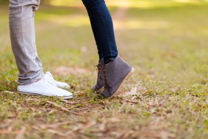 Teenage couple kissing outdoors at the park.