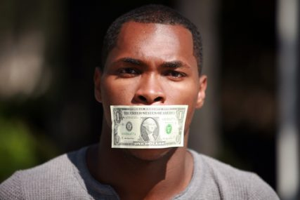 A young man wears a dollar bill taped over his mouth.
