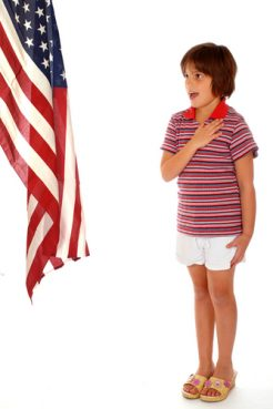 Elementary girl saying the Pledge of Allegiance toward a large American Flag.
