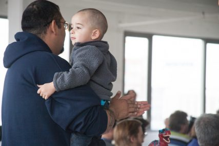 Dwight Solis holds his son, Bayne, while listening to speakers during Kansas City's first Oasis gathering on Sunday, April 6, 2014 in downtown Kansas City, Mo. Religion News Service photo by Sally Morrow