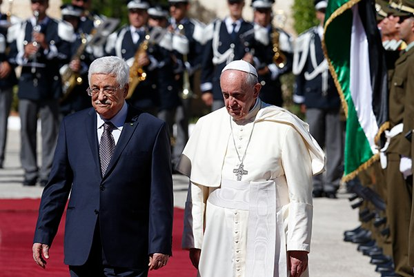 Pope Francis reviews the honor guard with Palestinian President Mahmoud Abbas during an arrival ceremony at the presidential palace in Bethlehem, West Bank, on May 25, 2014. Photo by Paul Haring, courtesy of Catholic News Service