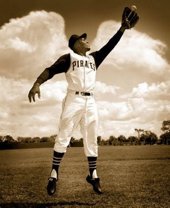 Framed by wing-shaped clouds, Roberto Clemente, the first Latin American inducted into the National Baseball Hall of Fame, jumps for a fly ball at Terry Park, where he played for the Pittsburgh Pirates. Photo by Jim Klingensmith courtesy of The Clemente Museum