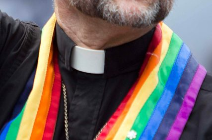 A priest wearing a rainbow-colored vestment makes an appearance during Toronto Pride in 2011.
