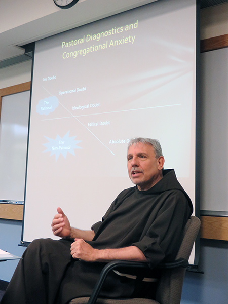 """The Rev. David Couturier, who consults with dioceses around the world on management issues, explains the principles of what he calls """"Franciscan economics"""" to nearly a dozen priests-in-training."""