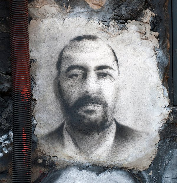A portrait of Abu Bakr al-Baghdadi, leader of The Islamic State, is rendered on the wall of a building in St. Romain, France.