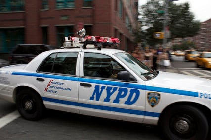 An NYPD car drives through the streets of New York City.