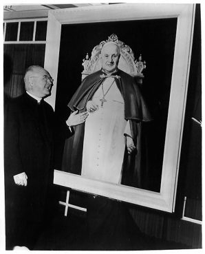 Francis Cardinal Spellman, Archbishop of New York, unveiled a life-sized portrait of Pope John XXIII at ceremonies here. Bernard Godwin, a New York artist, painted the portrait in Rome. It shows the Pope in red and white vestments. Commissioned by an unidentified New York business man, the 40-by-50-inch oil will be taken to Rome in June for the presentation to the Pope. It will be hung in the Pontifical North American College, where selected students from U.S. dioceses are sent to complete their training. (Date unknown.)