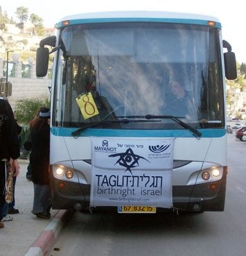Visitors board a Birthright Israel bus during their 10-day tour in 2003. Despite increased violence in the region, the tours have continued and visitors are accompanied by an armed security guard.