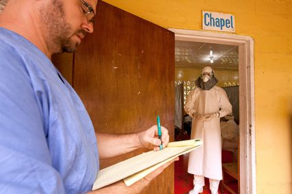 Kent Brantly of Samaritan's Purse, right, gives orders for medication to administer to the Ebola patients through the doorway of the isolation unit in Liberia. Dr. Brantly spent almost four hours in a Tyvek suit in order to care for the three patients in the unit.