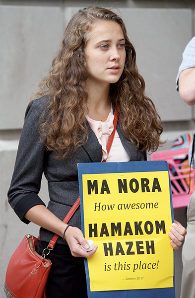 Emily Wirzba, program assistant for energy and environment, held a sign to help people with the words as they sang in Washington, D.C., on July 29, 2014.