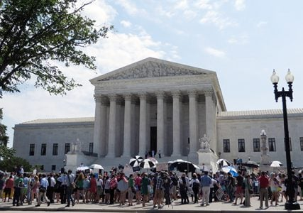 Citizens rallied on the steps of the Supreme Court on June 30, 2014, after it sided with the evangelical owners of Hobby Lobby Stores Inc., ruling 5-4 that the arts-and-crafts chain does not have to offer insurance for types of birth control that conflict with company owners' religious beliefs. RNS photo by Heather Adams