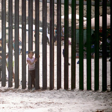 A Hispanic girl slips through the border fence separating the U.S. and Mexico at Border Field State Park in Southern California.