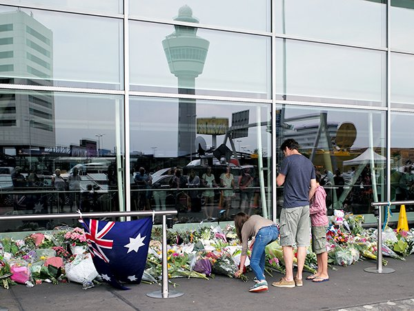 A family adds flowers to a growing memorial at Amsterdam Schiphol Airport. The memorial was erected for the victims of the Malaysian Airlines flight MH17, which crashed in the Ukraine on July 17, 2014, and killed all 298 people on board.