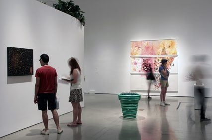 """Patrons peruse the artwork in """"Back to Eden: Contemporary Artists Wander the Garden,"""" an exhibit at New York's Museum of Biblical Art. Photo courtesy Gina Fuentes Walker"""