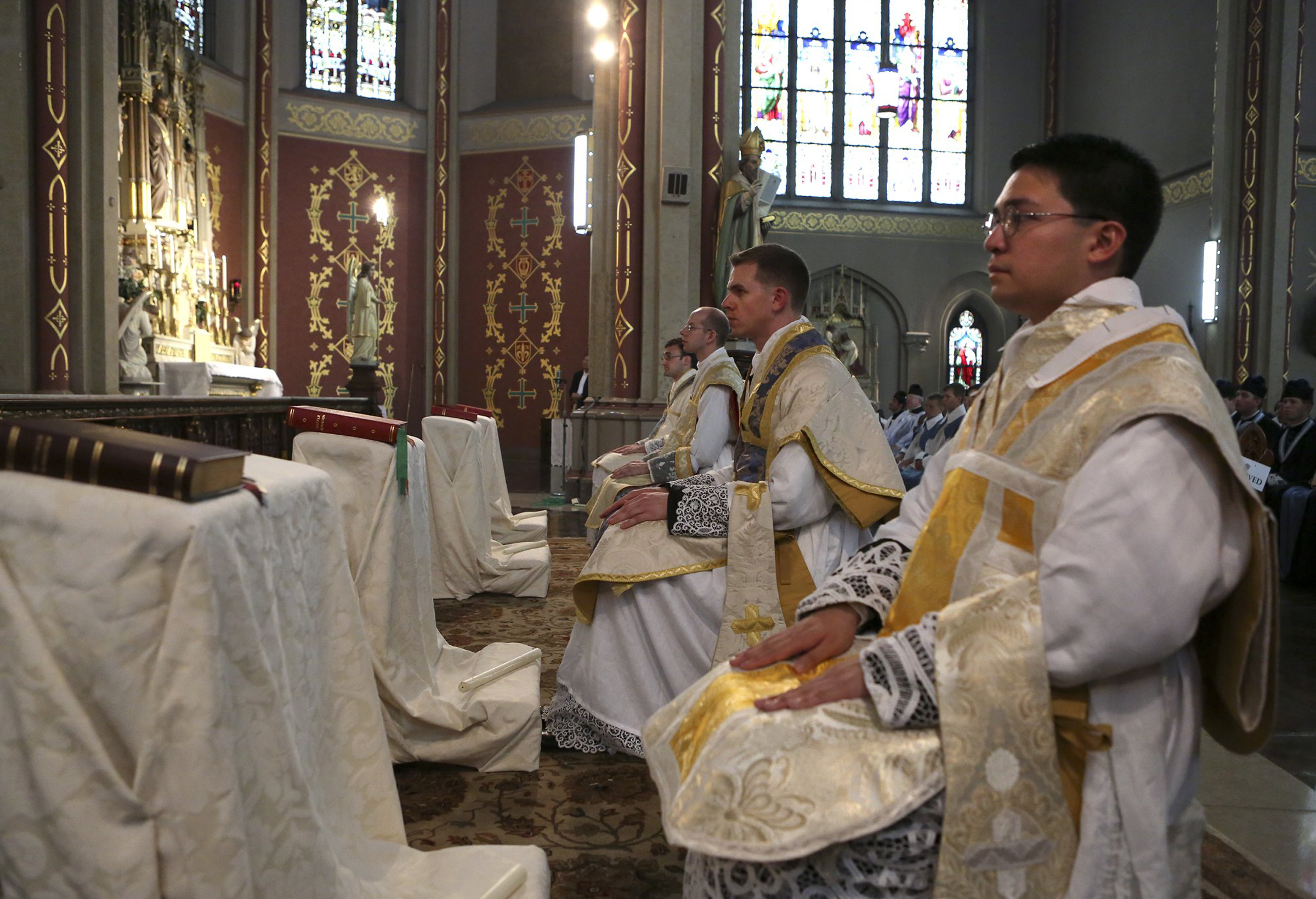 Right to left, Abbe Joel Estrada, Abbe Andrew Todd, Abbe Benjamin Coggeshall and Abbe Francis Altiere sit on the altar during their ordination at St. Francis de Sales on Tuesday (Aug. 5). The Mass was celebrated in Latin by Cardinal Raymond Burke, the former Archbishop of St. Louis. For use with RNS-LATIN-MASS, transmitted on August 6, 2014, Photo by Cristina Fletes-Boutte, St. Louis Post-Dispatch.