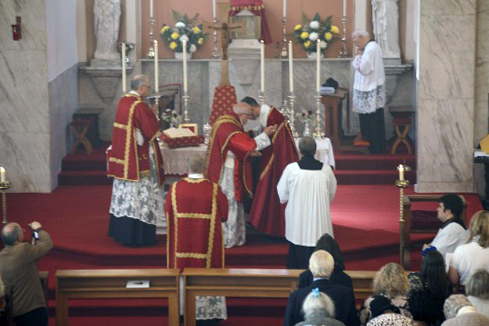 The sign of peace is exchanged at a Mass celebrated at Holywell, Wales, on July 6, 2014.