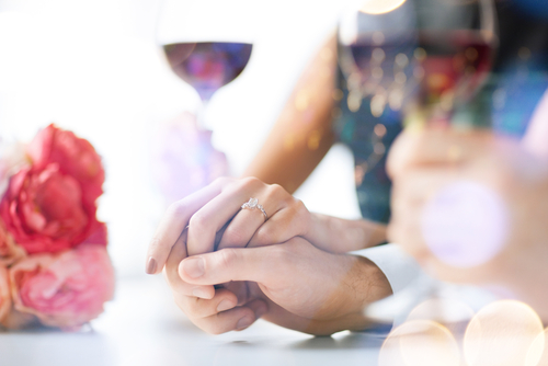 Engaged couple with wine glasses in restaurant.