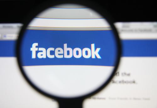 Facebook logo seen through a magnifying glass on a screen.