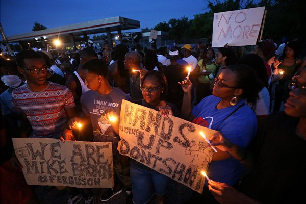 (RNS1-aug14) Left to right, Keith Lovett, Melik Smith, Victoria Smith, Linda Smith and Antonio McDonald, hold candles during a gathering of people at the QuikTrip in Ferguson, Mo., on Thursday (Aug. 14). For use with RNS-FERGUSON-VIGIL, transmitted on August 14, 2014, Photo By David Carson, courtesy of St. Louis Post-Dispatch.