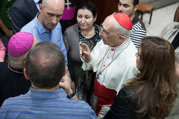 Catholic Relief Services head of programming Kris Ozar, on left in blue shirt, meets Cardinal Fernando Filoni and the delegation of Religious Christian leaders to assess what the needs of the refugees are and what needs to be done, at St.Ithilaha church in Duhok, Iraq.  Photo © Hawre Khalid / Metrography for Catholic Relief Services