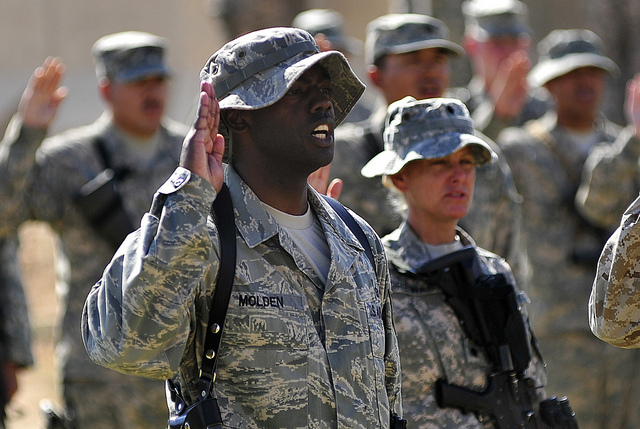 Tech. Sgt. LaMarcus Molden, 9th Air and Space Expeditionary Task Force-Iraq personnel manager, recites the oath of enlistment along with 125 other service members during a re-enlistment ceremony at Al Asad Air Base, Iraq on Oct. 5, 2011.