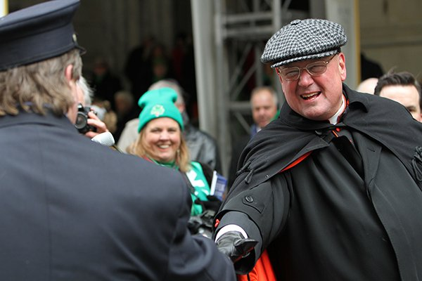 Cardinal Timothy M. Dolan of New York greets a New York City firefighter while reviewing the 253rd annual St. Patrick's Day in front of St. Patrick's Cathedral in New York on March 17, 2014. RNS photo by Gregory A. Shemitz