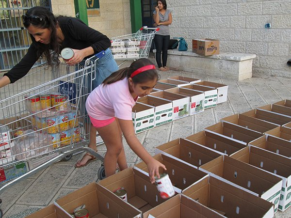 Volunteers pack food packages to be distributed to needy Israelis. Some worry it will be more difficult to obtain produce during the sabbatical year called shmita. Religion News Service photo by Michele Chabin