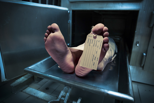 Grungy photo of feet with toe tag on a morgue table.