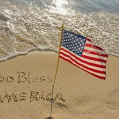 """""""God Bless America,"""" written in sand with an American flag."""