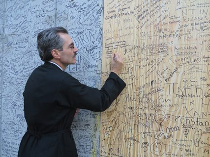 John Mamangakis signs a wall at the construction site where St. Nicholas Greek Orthodox Church plans to rebuild the church that was destroyed on 9/11, on Saturday (Oct. 18) in New York. Religion News Service photo by Sarah Pulliam Bailey