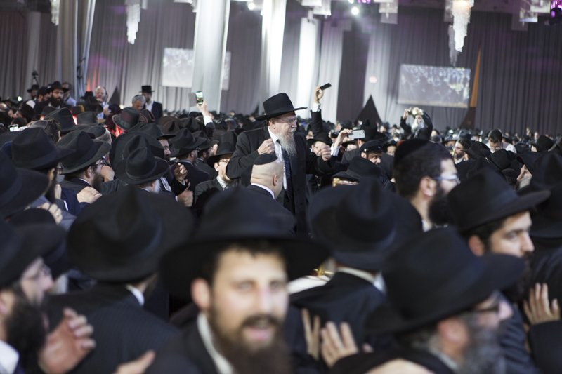 Rabbis are seen in this photo dancing with their colleagues at a banquet at the South Brooklyn Marine Terminal in the Brooklyn borough of New York on November 23, 2014. They are among 5,200 rabbis and guests from over 80 countries in New York for the International Conference of Chabad-Lubavitch Emissaries, an annual event aimed at reviving Jewish awareness and practice around the world. Photo by Adam Ben Cohen / Chabad.org