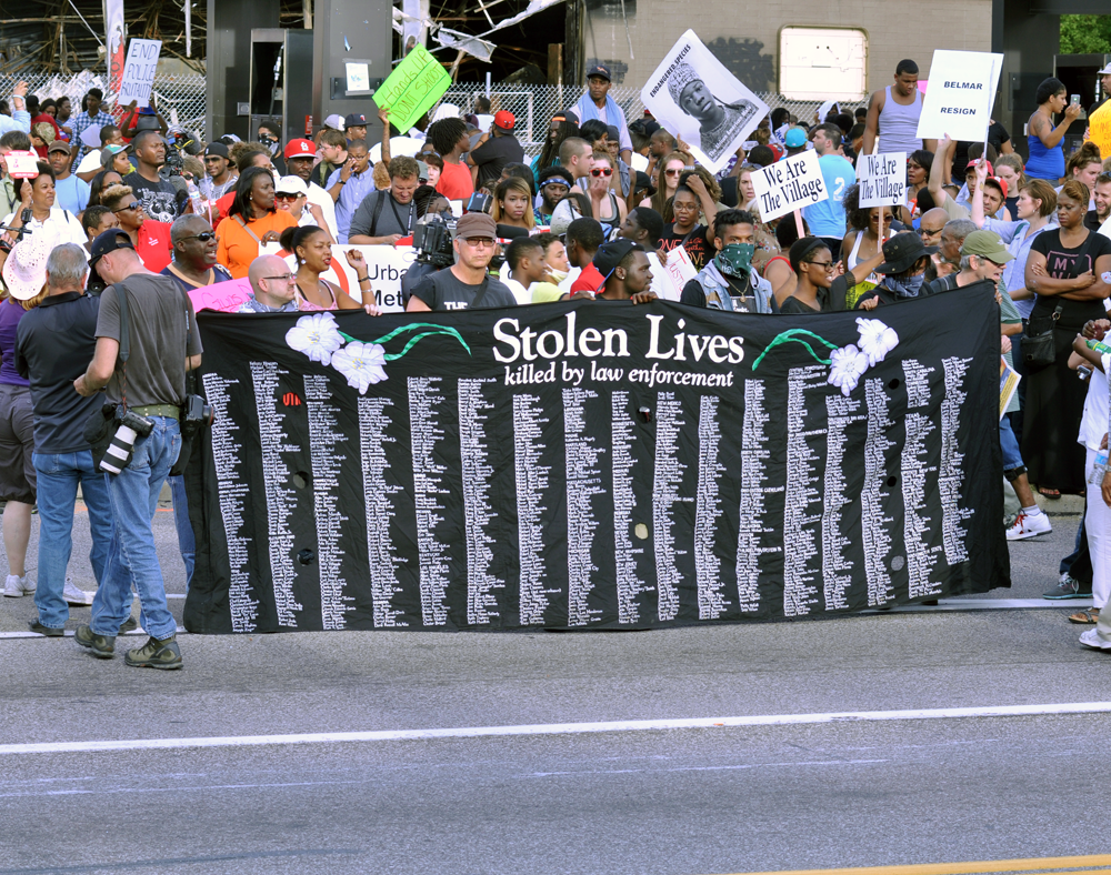 Protestors in Ferguson, MO on August 15, 2014, holding up a Stolen Lives Project banner listing people killed by police officers.