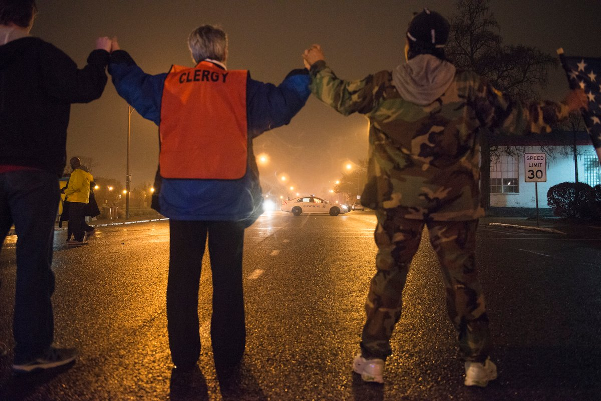 A clergy member holds hands with protestors as they shut down a street in St. Louis., on November 23, 2014. Photo by Justin L. Stewart
