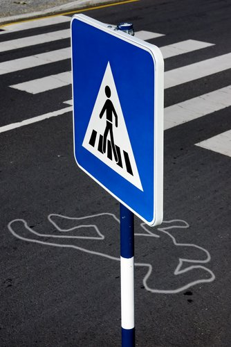 A sign for a pedestrian crosswalk next to a chalk outline of a person on the road.