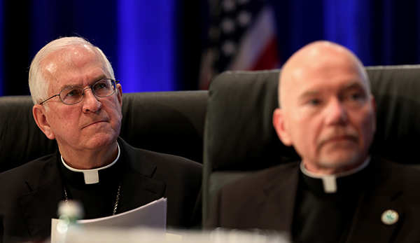 Archbishop Joseph E. Kurtz of Louisville, Ky., left, president of the U.S. Conference of Catholic Bishops, and Msgr. Ronny E. Jenkins, USCCB general secretary, listen to a speaker Monday (Nov. 10, 2014) during the bishops' annual fall general assembly in Baltimore. Photo by Bob Roller, courtesy of Catholic News Service