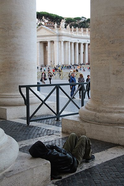 A homeless man sits under the right colonnade close to where the showers are going to be built in St. Peter's square at the Vatican on Thursday (Nov 13, 2014). Religion News Service photo by Josephine McKenna