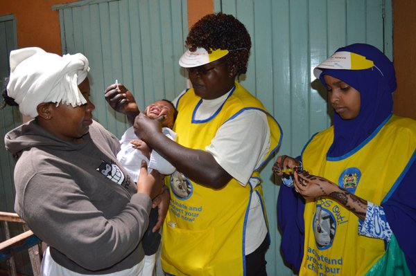 Health workers administer a vaccine to a baby in Nairobi's Mlango Kubwa area. Religion News Service photo by Fredrick Nzwili