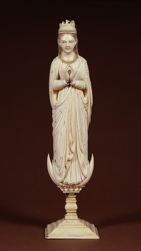 """Created in Ceylon, an island off the southeastern coast of India (now Sri Lanka), this piece represents a stoic Virgin that combines typical European attributes of the Immaculate Conception—crown and crescent moon—with the streamlined elegance and facial features of Indian sculpture. Unknown artist, """"Virgin of the Immaculate Conception,"""" ca. 1690–1710; Ceylon (present-day Sri Lanka); Ivory with gilt and polychromy, 10 1/8 in. high; Walters Art Museum; inv. 71.341. Photo courtesy of National Museum of Women in the Arts"""
