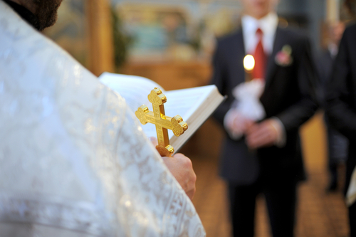 Priest holding a cross and Bible at wedding ceremony.