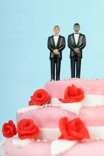 Wedding cake with groom figures on top.