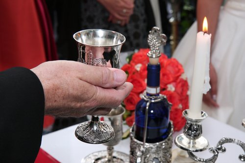 Rabbi holds kiddish cup with wine in front of a groom and bride.
