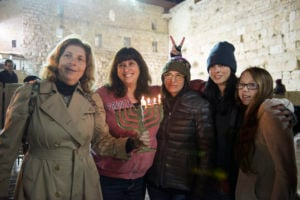 A photo of five women, including Sarah Silverman, holding a lit menorah at the Western Wall.