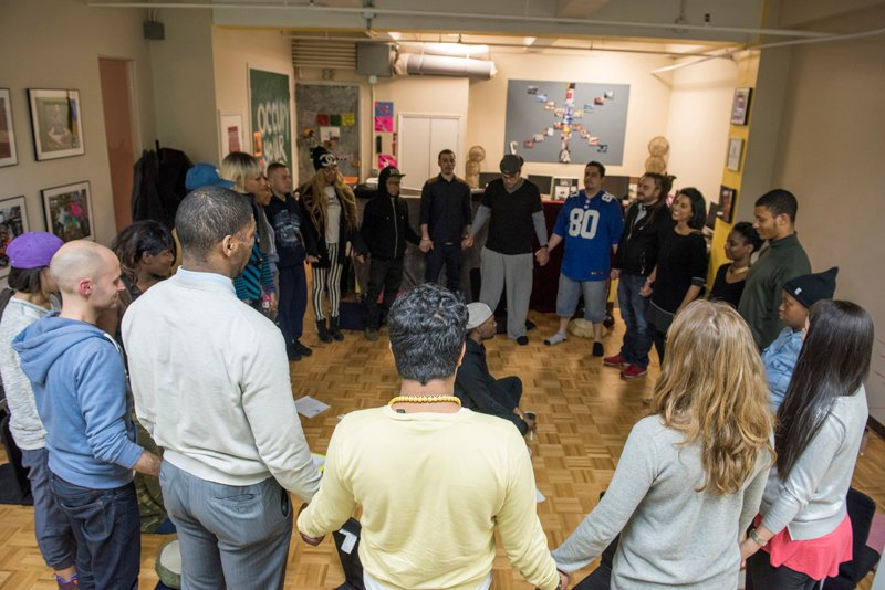 Participants hold hands during the closing ceremony at the end of the Urban Retreat at the Reciprocity Foundation. Photo by Alex Fradkin