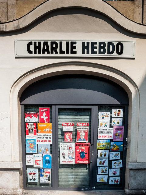 A Charlie Hebdo building with cartoons on the doors.