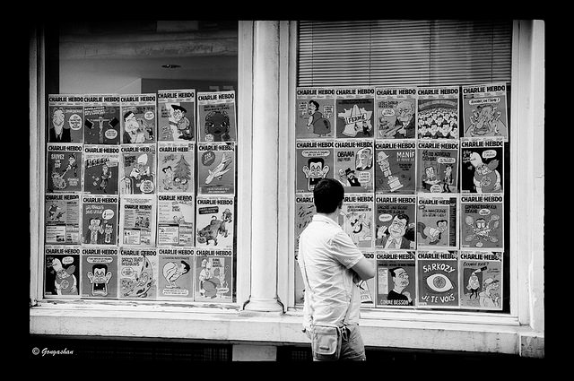 A man looks at Charlie Hebdo cartoons in a window.