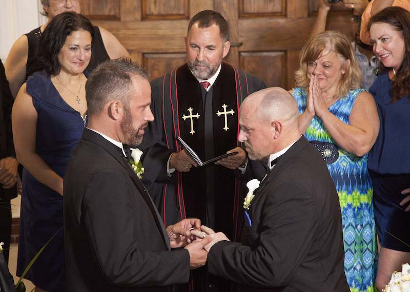 Aaron Huntsman (left) and William Lee Jones (right) are married in Key West, Fla., with the Rev. Steve Torrence officiating, the first couple ot marry in the Florida Keys. For use with RNS-GAY-MARRIAGE, transmitted Jan. 28, 2015. RNS photo courtesy REUTERS/Carol Tedesco/Florida Keys News Bureau. * Editors: This photo can only be used with RNS-GAY-MARRIAGE, originally transmitted Jan. 28, 2015.