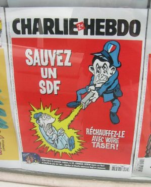 A magazine cover of Charlie Hebdo through a window.