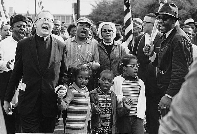 Civil Rights Movement Co-Founder Dr. Ralph David Abernathy and his wife Mrs. Juanita Abernathy follow with Dr. and Mrs. Martin Luther King as the Abernathy children march on the front line, leading the Selma to Montgomery march in 1965. The Children are Donzaleigh Abernathy in striped sweater, Ralph David Abernathy, 3rd and Juandalynn R. Abernathy in glasses. Name of the white Minister in the photo is unknown.